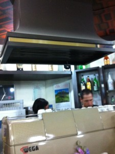 Una cappa aspirante sopra la macchina da caffè nel bar