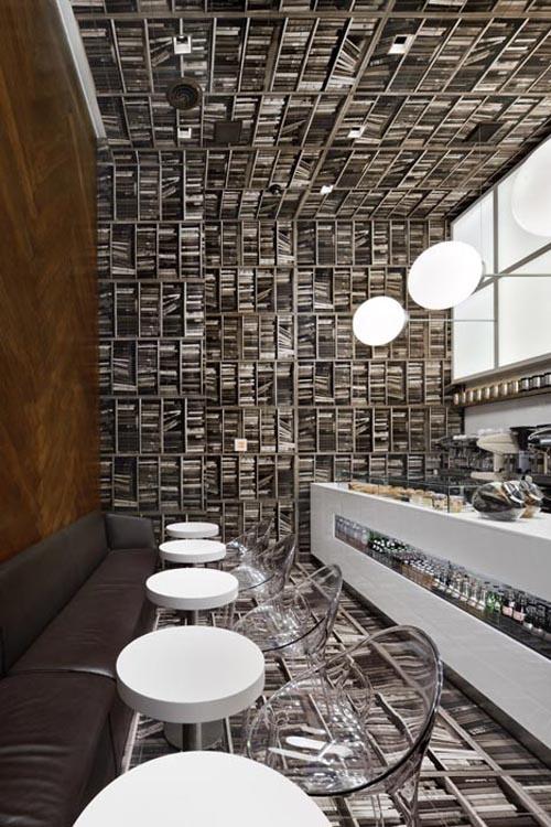 Una caffetteria rovesciata, con il pavimento sulle pareti e tantissimi libri ovunque. Vertiginoso!